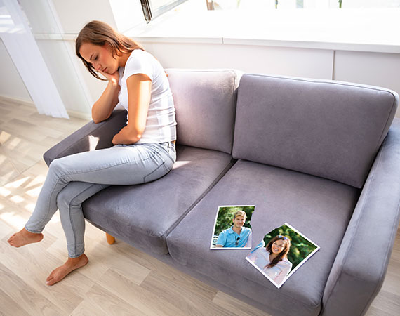 Woman sitting on sofa sad about breaking up with boyfriend and needs counselling