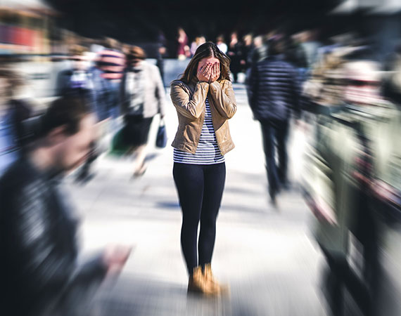Woman suffering from anxiety while out in crowded place